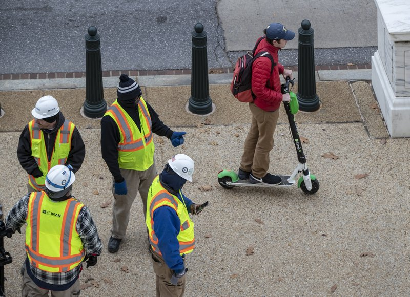 In this Dec. 5, 2018, photo a rider maneuvers a Lime brand electric scooter on a sidewalk past workers on Capitol Hill in Washington. (AP Photo/J. Scott Applewhite)