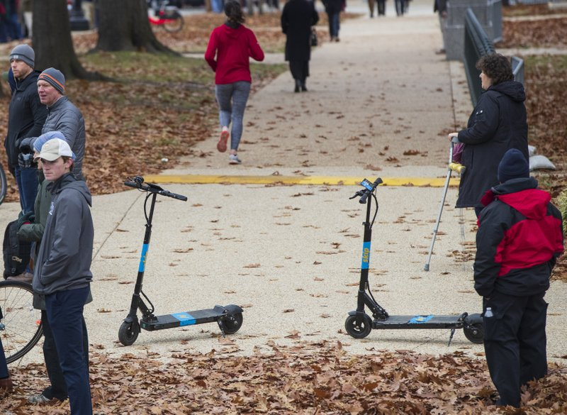In this Dec. 5, 2018, photo Skip brand electric scooters are left on a sidewalk on Capitol Hill in Washington. (AP Photo/J. Scott Applewhite)