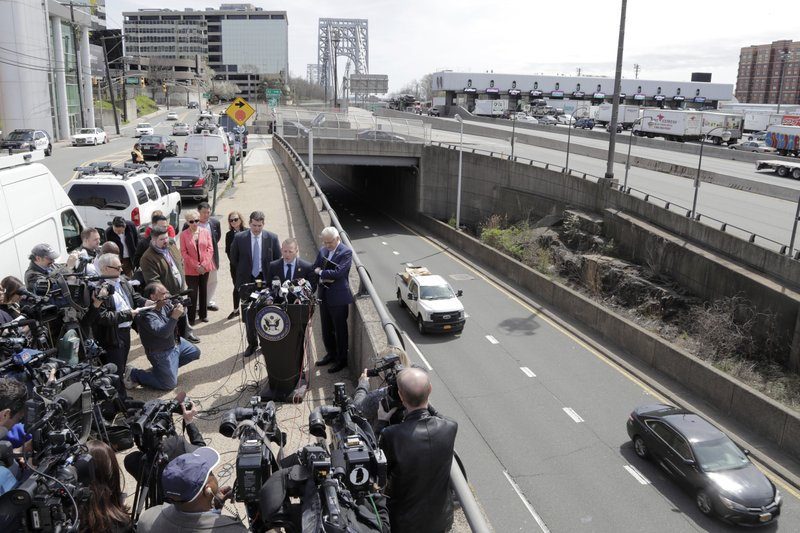 Reporters gather around U.S. Rep. Josh Gottheimer (NJ-5), standing at podium, as he speaks during a news conference near the George Washington Bridge talking about the congressman's plan to fight back against New York City's proposed congestion tax on New Jersey commuters, Wednesday, April 17, 2019, in Fort Lee, N. (NJ-9) announced legislation they say will ensure New Jersey motorists, who already pay up to $15 for bridge or tunnel tolls, won't be charged twice. New York's legislature approved a conceptual plan this month. that will allocate revenue to fix the city's mass transit system. New York would become the first American city to use so-called congestion pricing to reduce gridlock and fund mass transit improvements. (AP Photo/Julio Cortez)