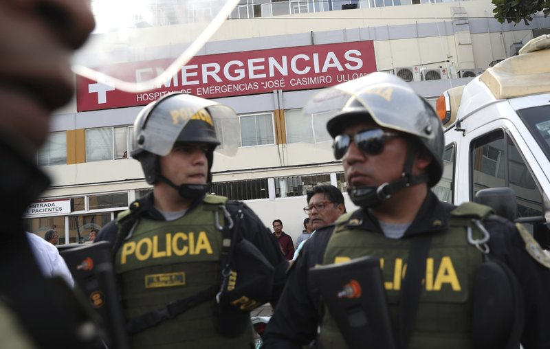 Police officers stand guard at the emergency entrance of the Casimiro Ulloa hospital where former Peruvian President Alan Garcia was taken after he shot himself, in Lima, Peru, Wednesday, April 17, 2019. (AP Photo/Martin Mejia)