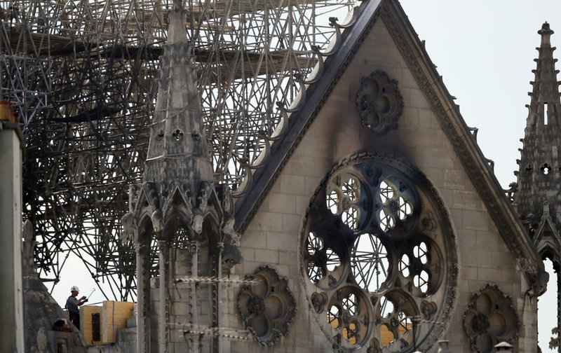A worker checks on a wooden support structure placed on the Notre Dame Cathedral in Paris, Wednesday, April 17, 2019. (AP Photo/Francois Mori)