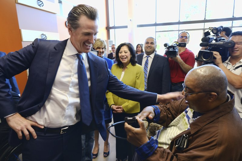 California Governor Gavin Newsom greets patient Joe Diaz, right, during a tour at the Rancho Los Amigos National Rehabilitation Center in Downey, Calif. (AP Photo/Richard Vogel)