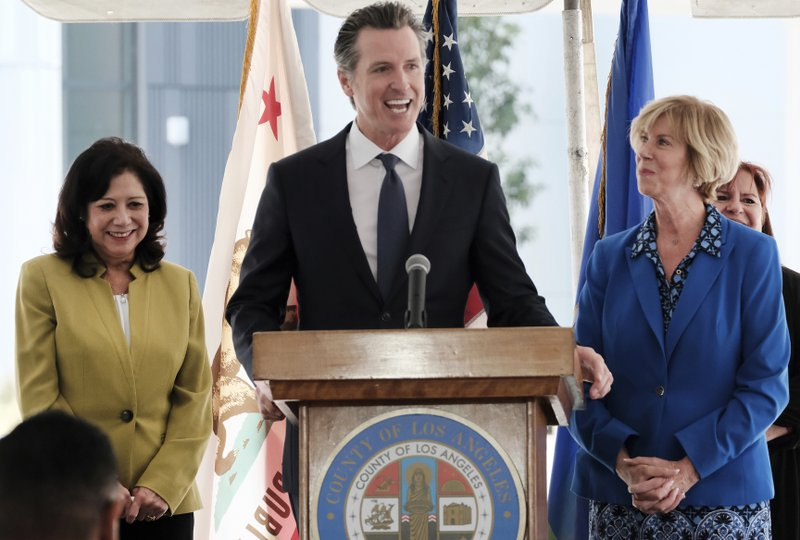 California Governor Gavin Newsom talks during a news conference while flanked by L.A. County Supervisor Hilda Solis,left and Chair of the Los Angeles County Board of Supervisors Janice Hahn at Rancho Los Amigos National Rehabilitation Center in Downey, Calif. (AP Photo/Richard Vogel)