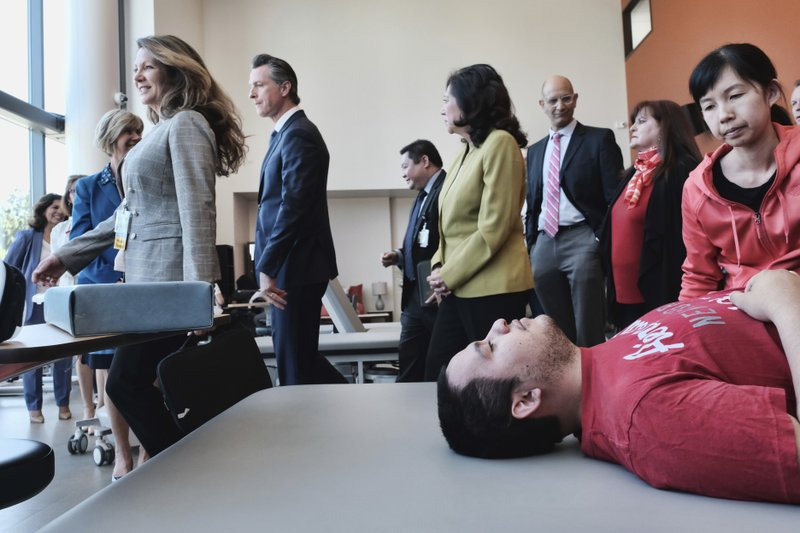 Led by Physical Therapist Mary Thompson, California Governor Gavin Newsom tour with L.A. County Supervisor Hilda Solis, center, at the Rancho Los Amigos National Rehabilitation Center in Downey, Calif. (AP Photo/Richard Vogel)