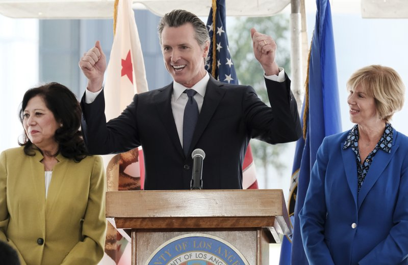 Gov. Gavin Newsom reacts during a news conference while flanked by L.A. County Supervisor Hilda Solis,left and Chair of the Los Angeles County Board of Supervisors Janice Hahn at Rancho Los Amigos National Rehabilitation Center in Downey, Calif. (AP Photo/Richard Vogel)