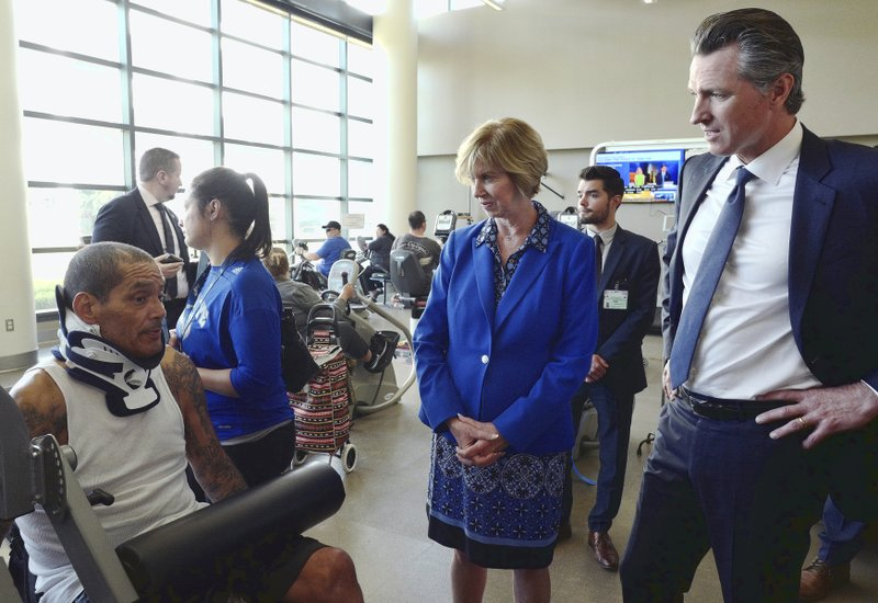California Governor Gavin Newsom, right, joined by Los Angeles County Board of Supervisors Janice Hahn, center talks with patient Detroit Farmer during a tour at the Rancho Los Amigos National Rehabilitation Center in Downey, Calif. (AP Photo/Richard Vogel