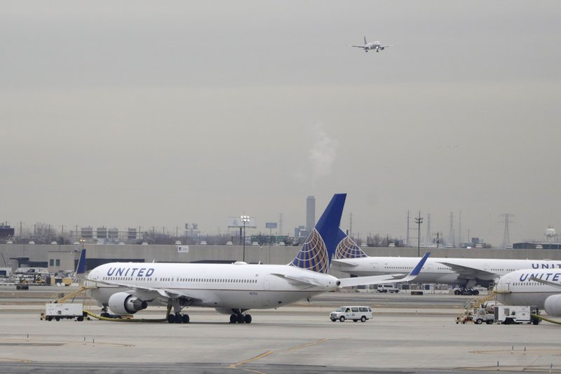 FILE - In this Jan. 23, 2019 file photo, United Airlines jets are seen as a plane approaches Newark Liberty International Airport, in Newark, N. (AP Photo/Julio Cortez, File)