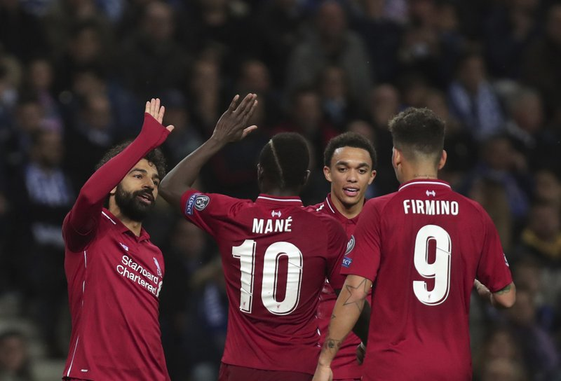 Liverpool's Mohamed Salah, left, celebrates with teammates after scoring his side's second goal during the Champions League quarterfinals, 2nd leg, soccer match between FC Porto and Liverpool at the Dragao stadium in Porto, Portugal, Wednesday, April 17, 2019. (AP Photo/Luis Vieira)
