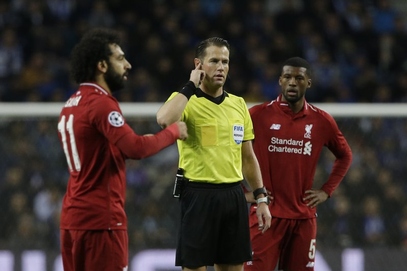 Referee Danny Makkelie, center, gets VAR assistance about a goal scored by Liverpool's Sadio Mane during the Champions League quarterfinal, 2nd leg, soccer match between FC Porto and Liverpool at the Dragao stadium in Porto, Portugal, Wednesday, April 17, 2019. (AP Photo/Armando Franca)