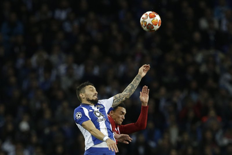 Porto defender Alex Telles, left, and Liverpool's Trent Alexander-Arnold jump for the ball during the Champions League quarterfinal, 2nd leg, soccer match between FC Porto and Liverpool at the Dragao stadium in Porto, Portugal, Wednesday, April 17, 2019. (AP Photo/Armando Franca)