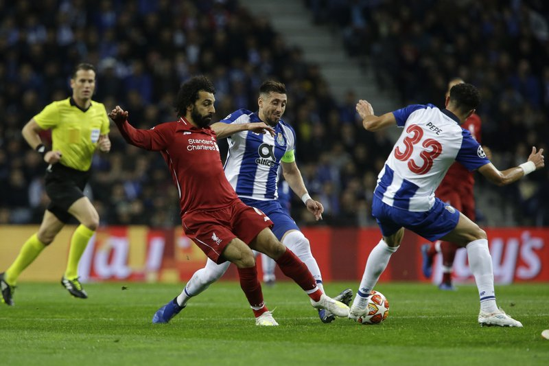 Liverpool's Mohamed Salah, left, challenges for the ball with Porto defender Pepe, right, and Porto midfielder Hector Herrera during the Champions League quarterfinal, 2nd leg, soccer match between FC Porto and Liverpool at the Dragao stadium in Porto, Portugal, Wednesday, April 17, 2019. (AP Photo/Armando Franca)