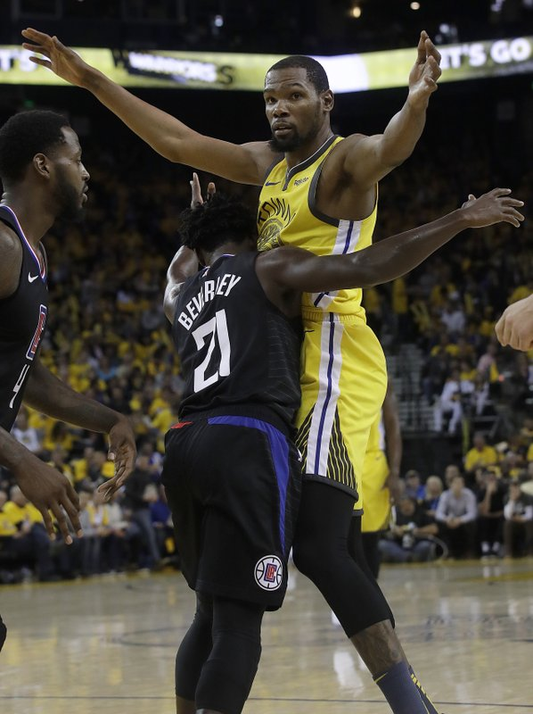 Golden State Warriors forward Kevin Durant, top, is defended by Los Angeles Clippers guard Patrick Beverley (21) during the second half of Game 2 of a first-round NBA basketball playoff series in Oakland, Calif. (AP Photo/Jeff Chiu)