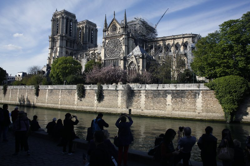 People watch Notre Dame cathedral, in Paris, Wednesday, April 17, 2019. Notre Dame Cathedral would have been completely burned to the ground in a