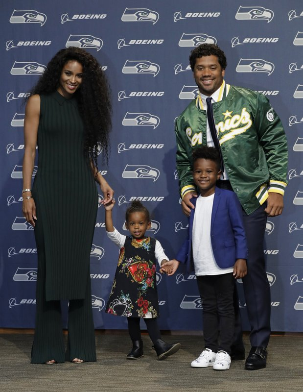 Seattle Seahawks NFL football quarterback Russell Wilson poses for photos with his wife Ciara, their daughter Sienna, and Ciara's son Future, Wednesday, April 17, 2019, in Renton, Wash. (AP Photo/Ted S. Warren)