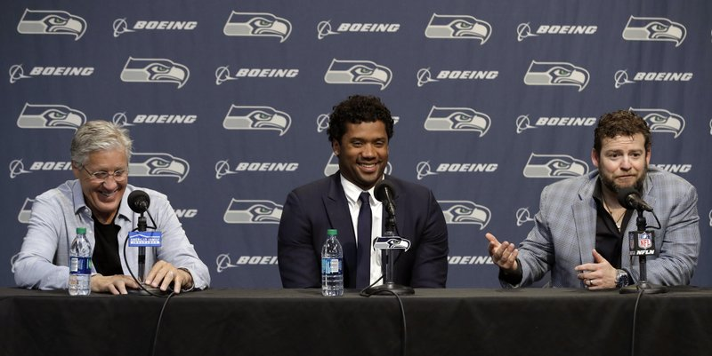 Seattle Seahawks NFL football quarterback Russell Wilson, center, talks to reporters along with head coach Pete Carroll, left, and general manager John Schneider, right, Wednesday, April 17, 2019, in Renton, Wash. (AP Photo/Ted S. Warren)