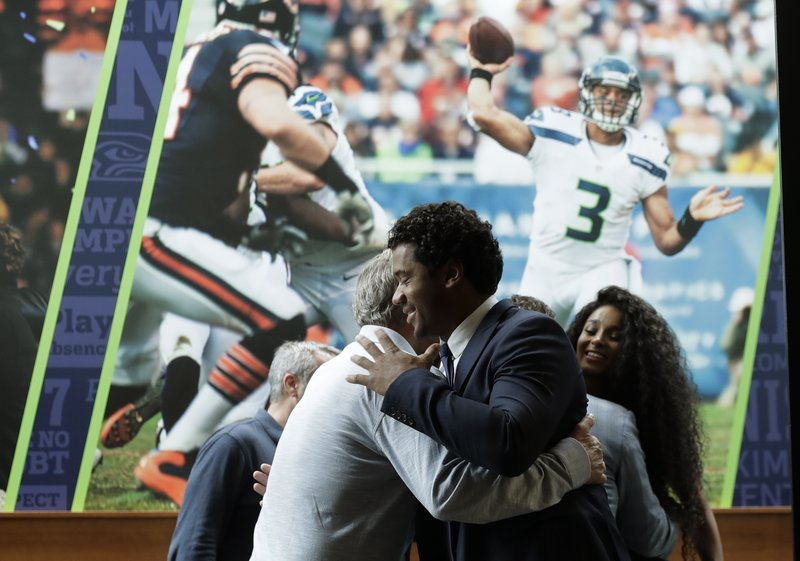Seattle Seahawks quarterback Russell Wilson, center, hugs head coach Pete Carroll, left, in front of a photograph of Wilson in action, as Wilson's wife Ciara looks on at right, Wednesday, April 17, 2019, prior to a NFL football press conference in Renton, Wash. (AP Photo/Ted S. Warren)