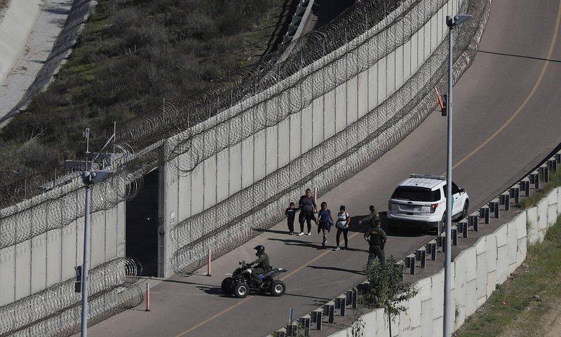 FILE - In this Dec. 16, 2018, file photo, Honduran asylum seekers are taken into custody by U.S. Border Patrol agents after the group crossed the U. (AP Photo/Moises Castillo, File)