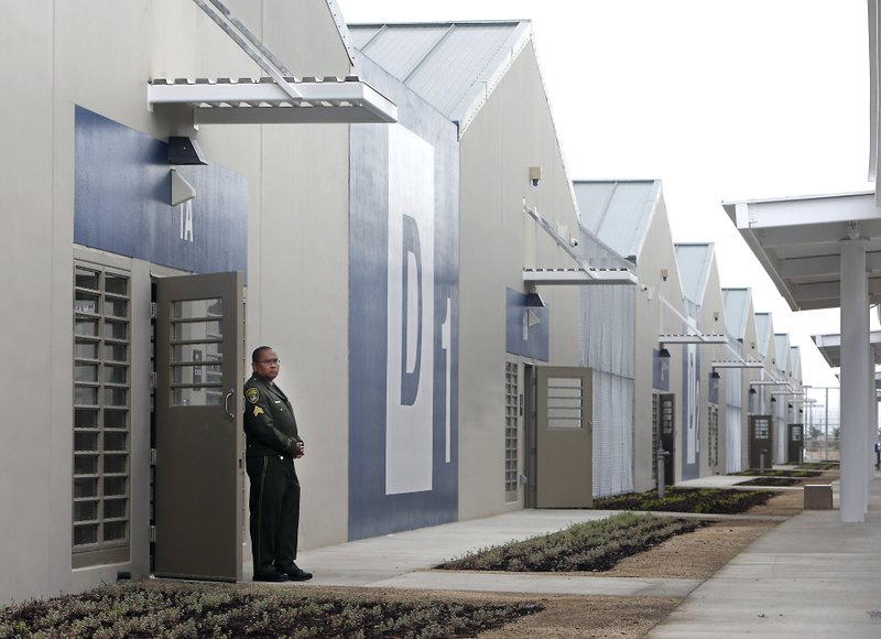 FILE - In this June 25, 2013 file photo, a correctional officer stands outside of one of the secure housing units at the new California Correctional Health Care Facility in Stockton, Calif. (AP Photo/Rich Pedroncelli, File)