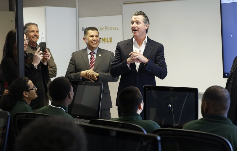 FILE - In this Jan. 22, 2019 file photo, Gov. Gavin Newsom, right, addresses youthful offenders taking a computer coding class at the O. (AP Photo/Rich Pedroncelli, File)