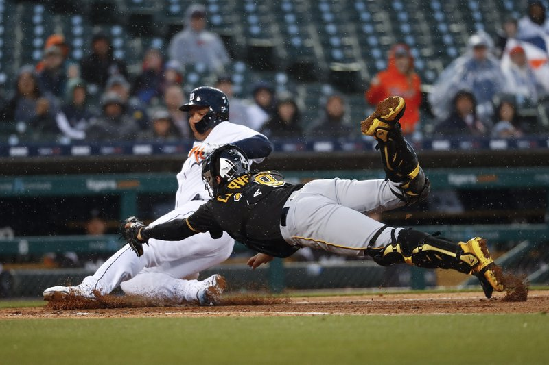 Detroit Tigers' Miguel Cabrera slides safely into home plate ahead of the tag of a diving Pittsburgh Pirates catcher Francisco Cervelli on a Ronny Rodriguez sacrifice fly in the fourth inning of a baseball game in Detroit, Wednesday, April 17, 2019. (AP Photo/Paul Sancya)