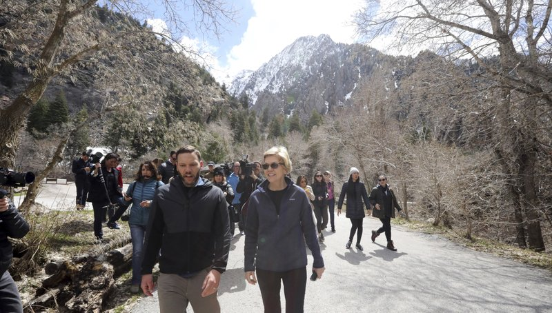 Democratic presidential candidate Sen. Elizabeth Warren, D-Mass., walks with Carl Fisher, of Save Our Canyons, during an visit to Big Cottonwood Canyon Wednesday, April 17, 2019, east of Salt Lake City. (AP Photo/Rick Bowmer)