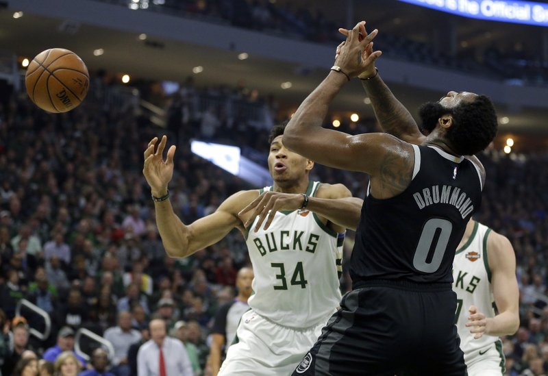 Detroit Pistons' Andre Drummond (0) and Milwaukee Bucks' Giannis Antetokounmpo (34) go for a loose ball during the first half of Game 2 of an NBA basketball first-round playoff series Wednesday, April 17, 2019, in Milwaukee. (AP Photo/Aaron Gash)