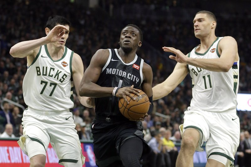 Detroit Pistons' Reggie Jackson, middle, drives between Milwaukee Bucks' Ersan Ilyasova (77) and Brook Lopez (11) during the first half of Game 2 of an NBA basketball first-round playoff series Wednesday, April 17, 2019, in Milwaukee. (AP Photo/Aaron Gash)
