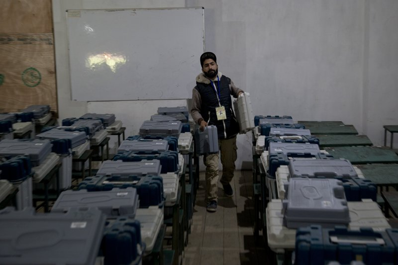 A Kashmiri polling official carries electronic voting machines and other election material for distribution on the eve of the second phase of India's general election inside a distribution center in Srinagar, Indian controlled Kashmir, Wednesday, April 17, 2019. (AP Photo/Dar Yasin)