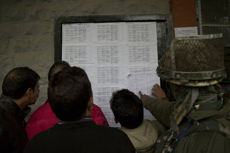 Kashmiri polling officials and Indian paramilitary soldiers check their duty roster posted on a wall on the eve of the second phase of India's general election in Srinagar, Indian controlled Kashmir, Wednesday, April 17, 2019. (AP Photo/Dar Yasin)