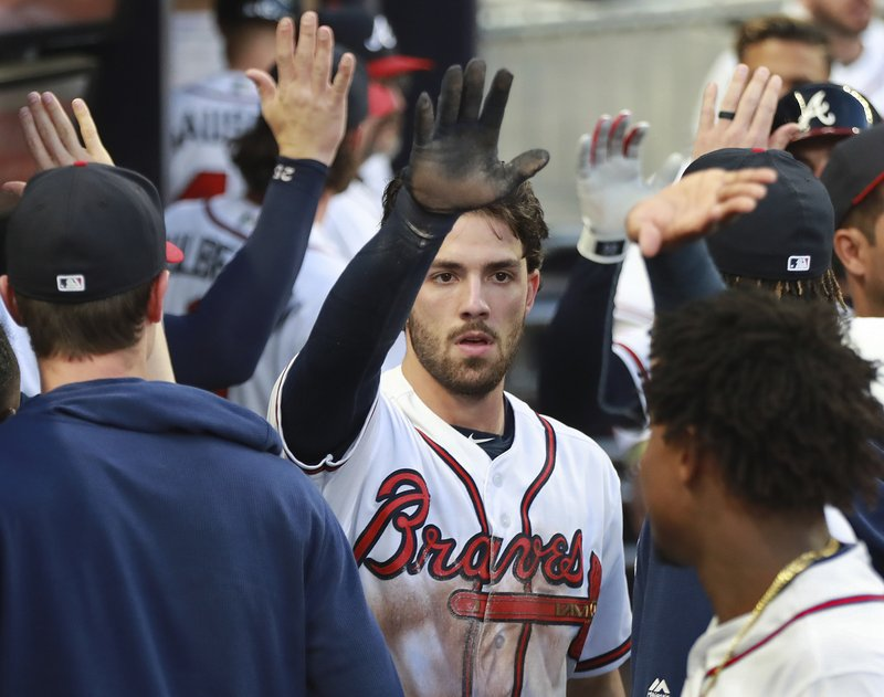 Atlanta Braves' Dansby Swanson gets high-fives in the dugout scoring on a double by Brian McCann against the Arizona Diamondbacks during the second inning of a baseball game Wednesday, April 17, 2019, in Atlanta. (Curtis Compton/Atlanta Journal-Constitution via AP)