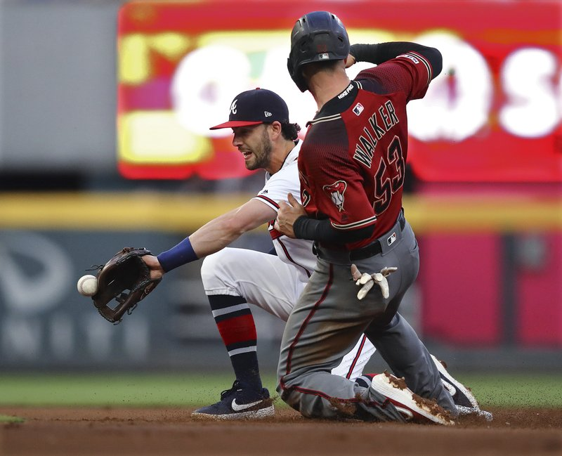 Arizona Diamondbacks Christian Walker steals second, beating the throw to Atlanta Braves shortstop Dansby Swanson during the second inning of a baseball game Wednesday, April 17, 2019, in Atlanta. (Curtis Compton/Atlanta Journal-Constitution via AP)
