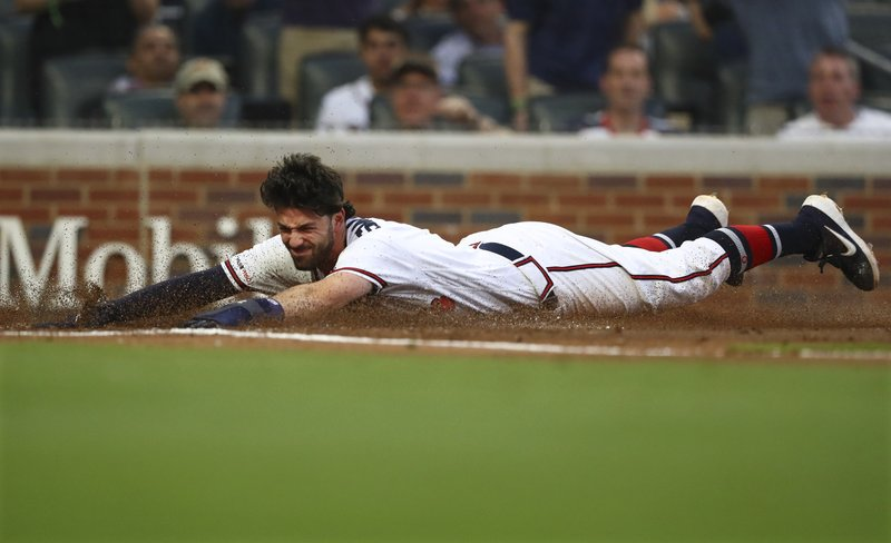 Atlanta Braves shortstop Dansby Swanson slides home to score on a double by Brian McCann against the Arizona Diamondbacks during the second inning of a baseball game Wednesday, April 17, 2019, in Atlanta. (Curtis Compton/Atlanta Journal-Constitution via AP)