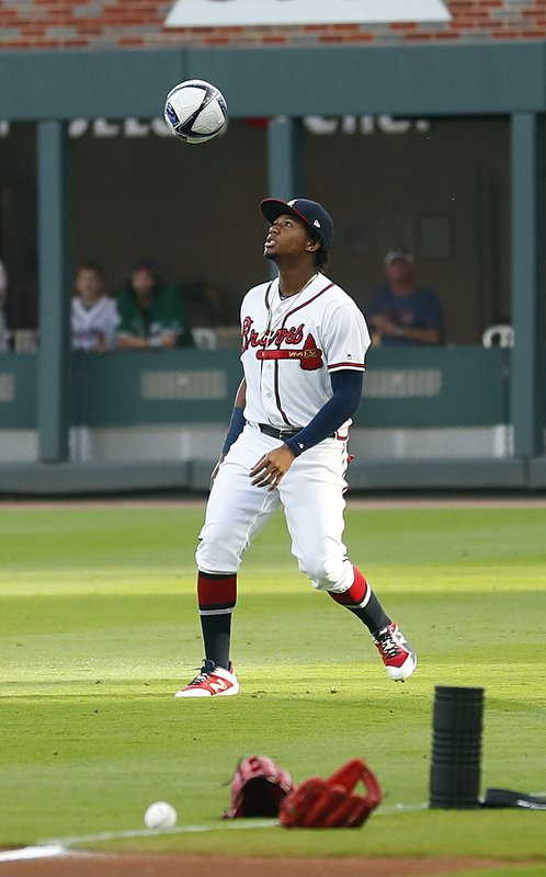 Atlanta Braves left fielder Ronald Acuna Jr. plays with a soccer ball before the team's baseball game against the Arizona Diamondbacks on Wednesday, April 17, 2019, in Atlanta. (AP Photo/John Bazemore)