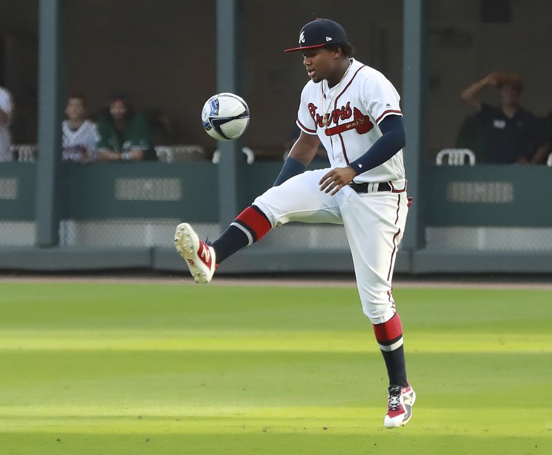 Atlanta Braves' Ronald Acuna Jr. kicks around a soccer ball in the outfield while the team recognizes the Atlanta United team for winning the MLS Cup, before playing the Arizona Diamondbacks in a baseball game Wednesday, April 17, 2019, in Atlanta. (Curtis Compton/Atlanta Journal-Constitution via AP)
