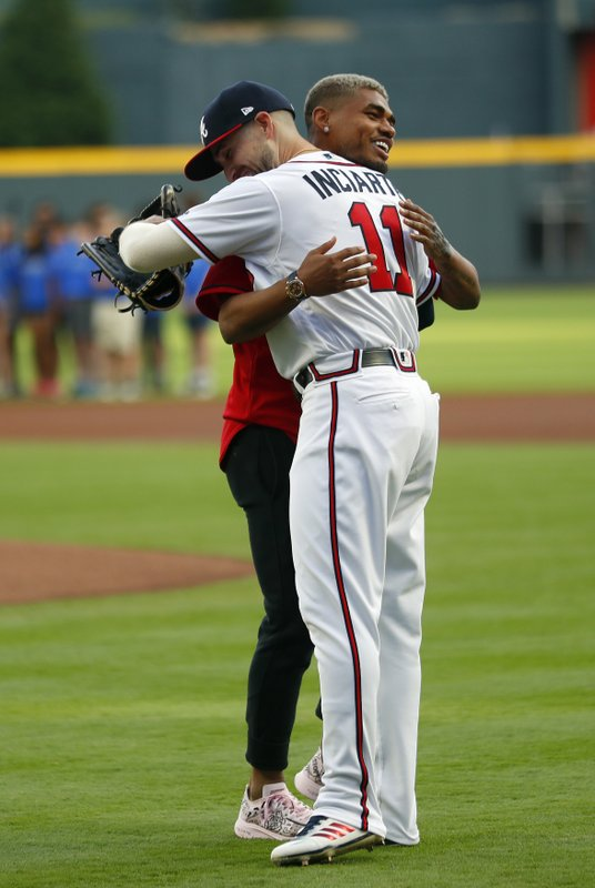 Atlanta United forward Josef Martinez embraces Atlanta Braves center fielder Ender Inciarte (11) after throwing out the ceremonial first pitch before a baseball game between the Arizona Diamondbacks and the Braves on Wednesday, April 17, 2019, in Atlanta. (AP Photo/John Bazemore)