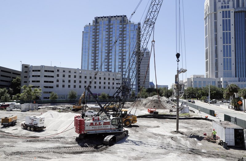 In this Tuesday, April 16, 2019, photo, construction begins on a new building in downtown Orlando, Fla. (AP Photo/John Raoux)