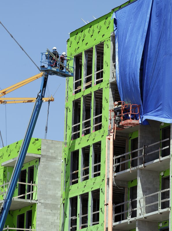 In this Tuesday, April 16, 2019, photo, workers labor at an apartment building near downtown Orlando, Fla. (AP Photo/John Raoux)