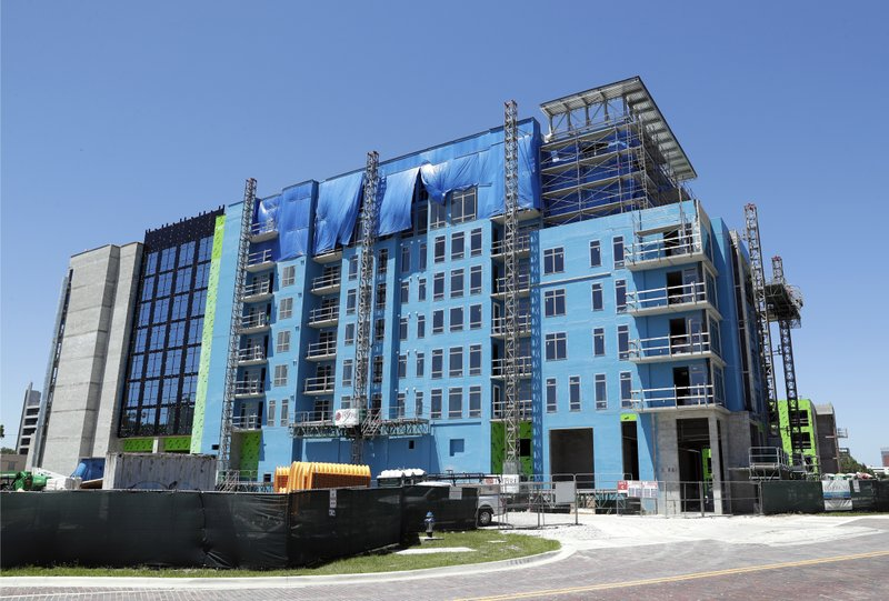 In this Tuesday, April 16, 2019, photo, an apartment building under construction nears completion in downtown Orlando, Fla. (AP Photo/John Raoux)
