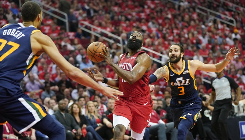 Houston Rockets guard Eric Gordon passes the ball as he drives against Utah Jazz center Rudy Gobert (27) and guard Ricky Rubio (3) during the first half of Game 2 of a first-round NBA basketball playoff series in Houston, Wednesday, April 17, 2019. (AP Photo/David J. Phillip)