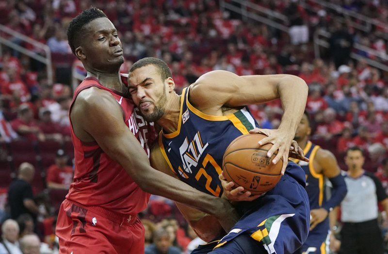 Utah Jazz center Rudy Gobert (27) is defended by Houston Rockets' Clint Capela during the first half of Game 2 of a first-round NBA basketball playoff series in Houston, Wednesday, April 17, 2019. (AP Photo/David J. Phillip)
