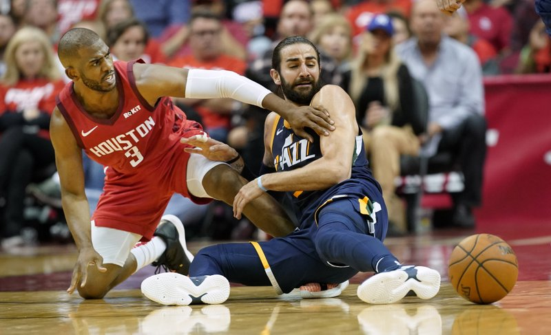 Houston Rockets' Chris Paul, left, battles for a loose ball with Utah Jazz guard Ricky Rubio during the second half of Game 2 of a first-round NBA basketball playoff series in Houston, Wednesday, April 17, 2019. (AP Photo/David J. Phillip)