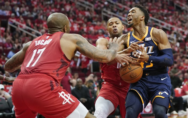 Houston Rockets defenders PJ Tucker (17) and Eric Gordon, center, block the path of Utah Jazz guard Donovan Mitchell, right, during the second half of Game 2 of a first-round NBA basketball playoff series in Houston, Wednesday, April 17, 2019. (AP Photo/David J. Phillip)