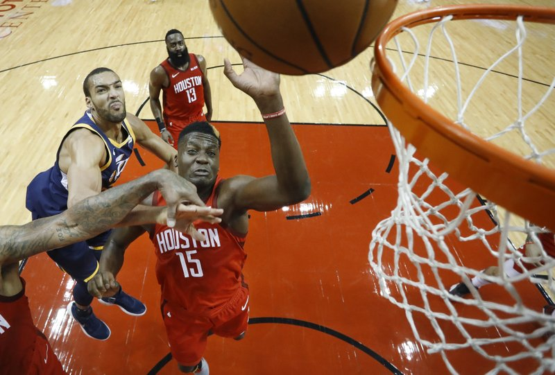 Houston Rockets' Clint Capela (15) reaches for a rebound in front of Utah Jazz center Rudy Gobert, left, during the first half of Game 2 of a first-round NBA basketball playoff series in Houston, Wednesday, April 17, 2019. (AP Photo/David J. Phillip)
