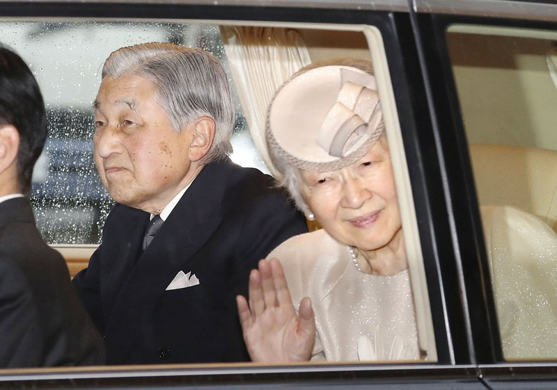 Japan's Emperor Akihito sits as Empress Michiko waves from a car on their way to visiting Ise Grand Shrine, or Ise Jingu, in Ise, central Japan, Wednesday, April 17, 2019. (Kyodo News via AP)