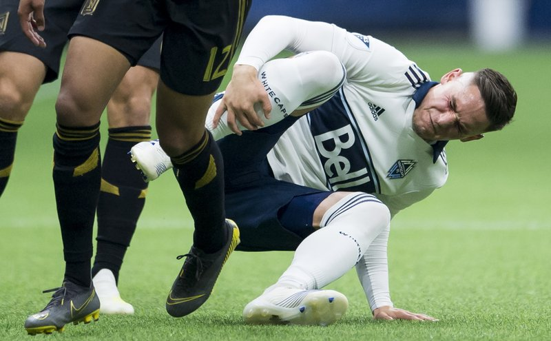 Vancouver Whitecaps defender Jake Nerwinski (28) holds his leg as he falls to the pitch after fighting for control of the ball against Los Angeles FC midfielder Niko Hamalainen (12) during the second half of an MLS soccer match Wednesday, April 17, 2019, in Vancouver, British Columbia. (Jonathan Hayward/The Canadian Press via AP)