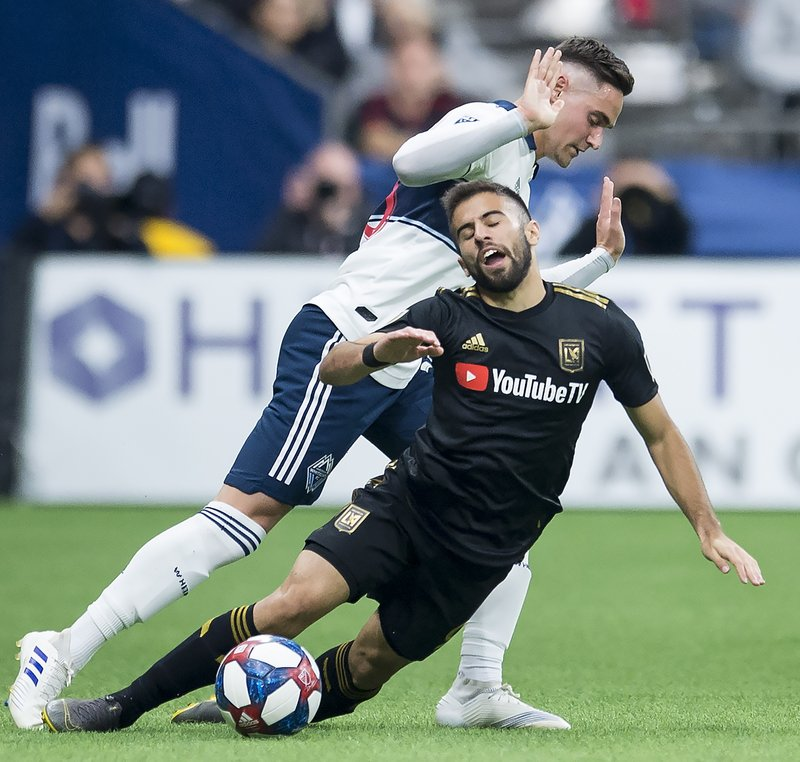 Vancouver Whitecaps defender Jake Nerwinski, top, fights for control of the ball with Los Angeles FC forward Diego Rossi (9) during the second half of an MLS soccer match Wednesday, April 17, 2019, in Vancouver, British Columbia. (Jonathan Hayward/The Canadian Press via AP)