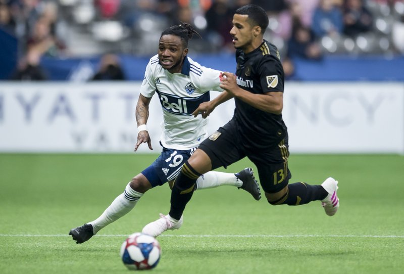 Vancouver Whitecaps forward Alhassane Bangoura (19) vies for control of the ball with Los Angeles FC defender Mohamed El-Munir (13) during the second half of an MLS soccer match Wednesday, April 17, 2019, in Vancouver, British Columbia. (Jonathan Hayward/The Canadian Press via AP)