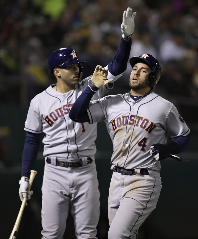 Houston Astros' George Springer (4) is congratulated by Carlos Correa, left, after scoring against the Oakland Athletics during the sixth inning of a baseball game Wednesday, April 17, 2019, in Oakland, Calif. (AP Photo/Ben Margot)