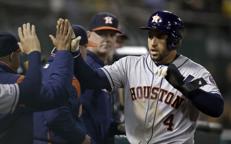 Houston Astros' George Springer (4) is congratulated after scoring against the Oakland Athletics during the sixth inning of a baseball game Wednesday, April 17, 2019, in Oakland, Calif. (AP Photo/Ben Margot)