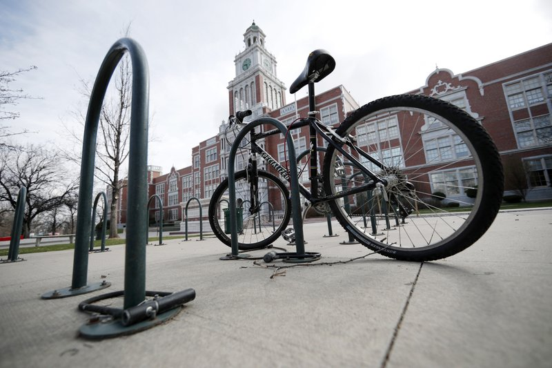 A lone bicycle stands in the rack outside East High School, Wednesday, April 17, 2019, in Denver. Denver-area public schools closed Wednesday as the FBI hunted for an armed young Florida woman who was allegedly